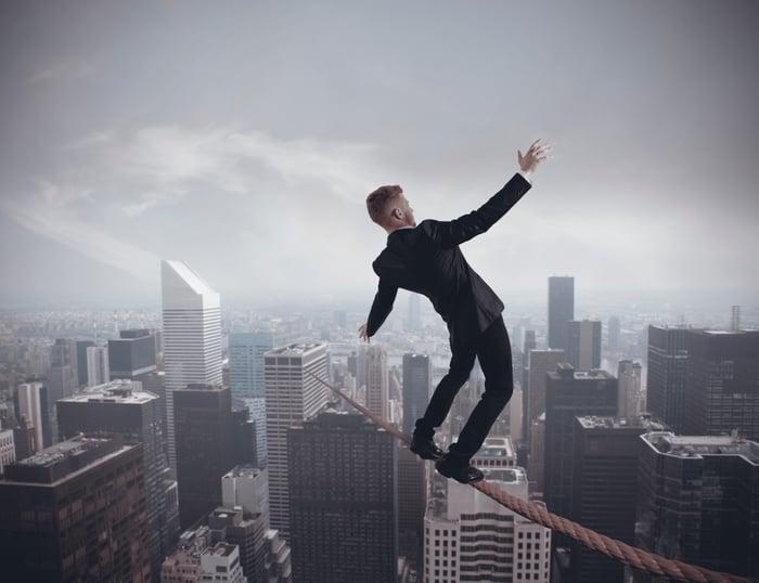 A businessman balances precariously on a wire high above a cituscape.
