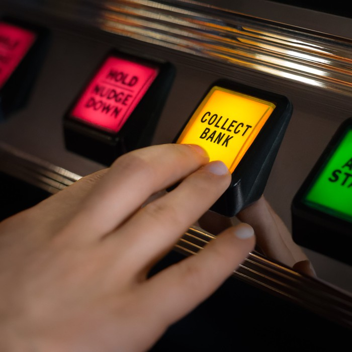 """A hand pushes a yellow button marked """"Collect Bank"""" on a casino-style machine."""