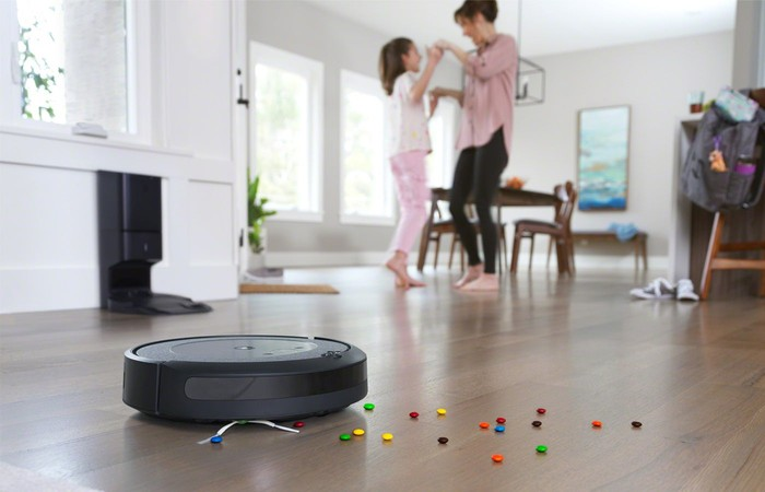 A Roomba cleans up candy as a mother dances with her daughter.