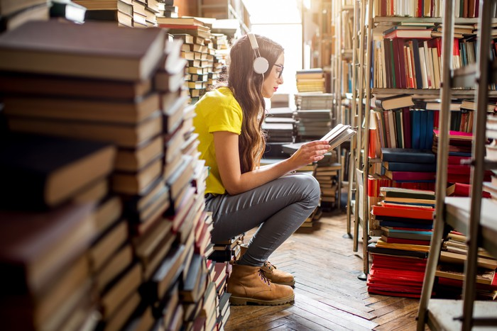 A young woman listens to music in a library.