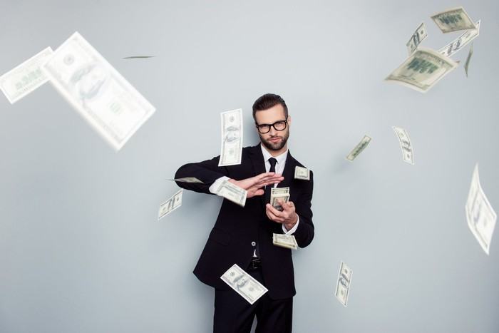 """A man in glasses throwing bills in the air off of a stack he is holding, making it """"rain."""""""