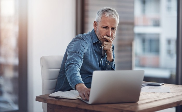 Man with serious expression looking at laptop