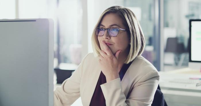 Smiling woman looking at computer screen
