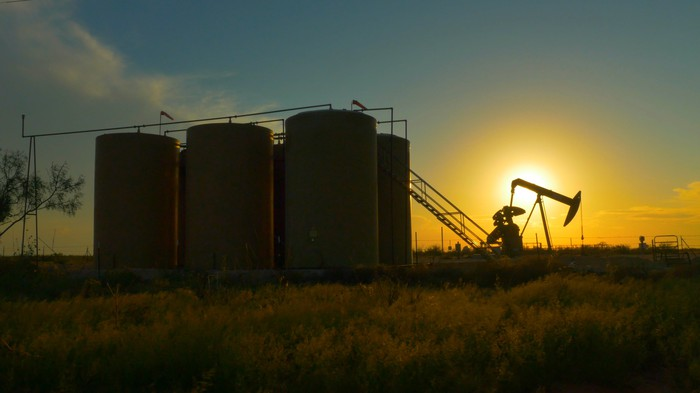 Oil storage tanks near a pumpjack and the sun in the background.