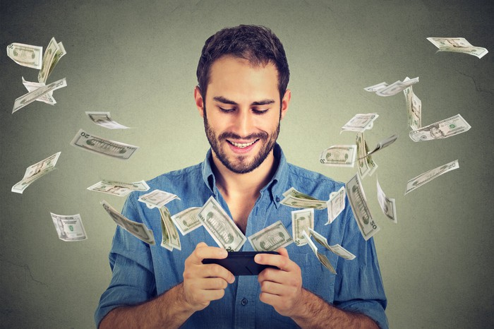 Cash flying from the screen of a smartphone held by a smiling person.