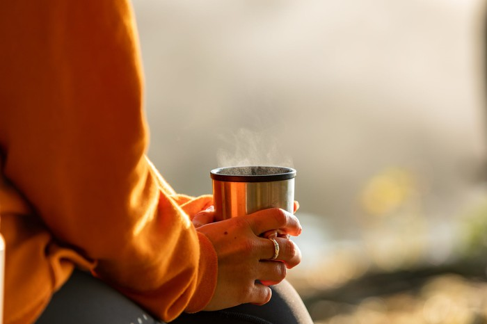 Person holding a steaming mug outside.