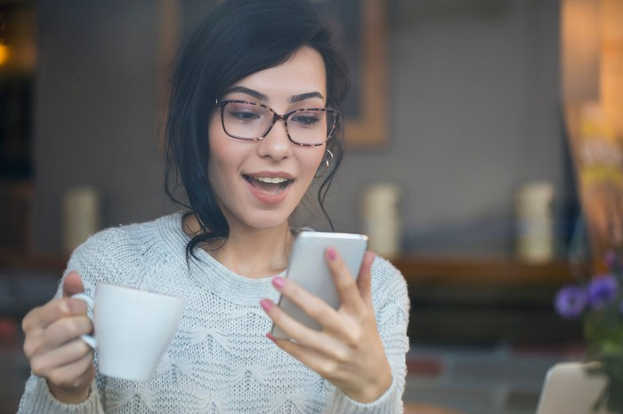 Woman looking excitedly at her smartphone while holding a mug.