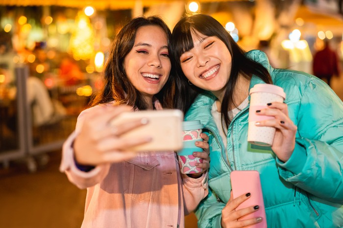Two young women take a selfie  in jackets  in an outdoor shopping area.