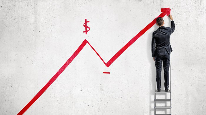 Red line with arrow trending up with a dollar sign drawn above the line and a man wearing a suit standing on a ladder holding his hand up to the arrow