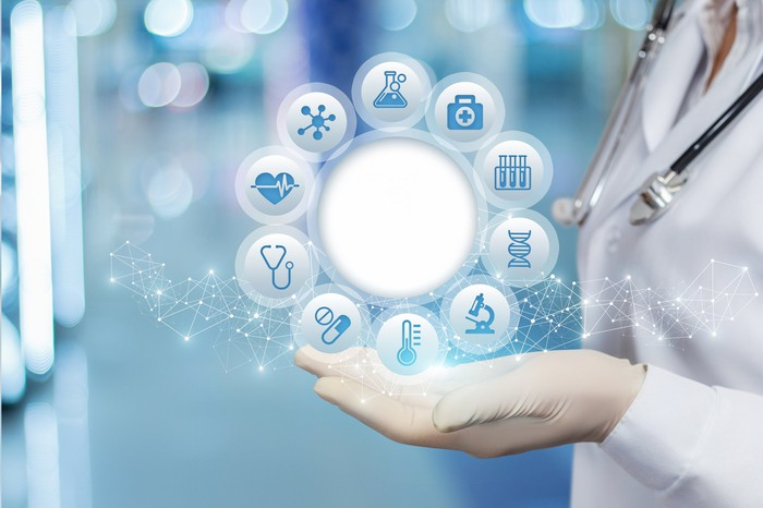 Images of healthcare-related icons displaying above a doctor's palm
