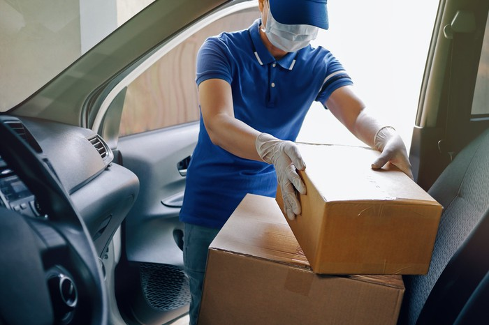 A man in mask and latex gloves taking delivery boxes out of a van.