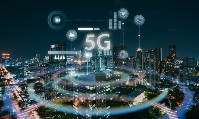 The letter 5G rise from a nighttime cityscape with other virtual icons.
