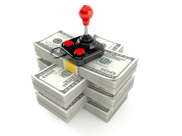 A video game joystick on top of a pile of money.