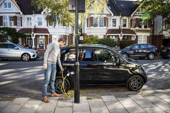 Man charging his car at a light post