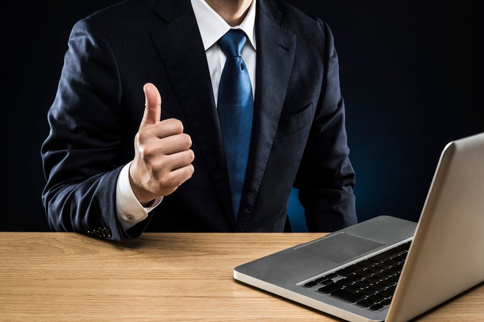 Man wearing coat and tie giving a thumbs up in front of a laptop