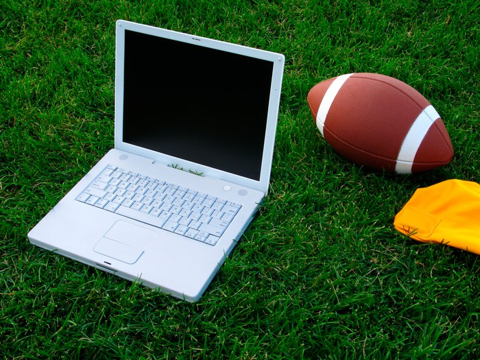 A football and a laptop sitting in grass.