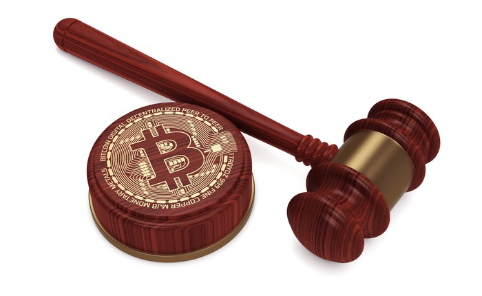 A judge's gavel resting next to a wooden stand marked with the bitcoin symbol.