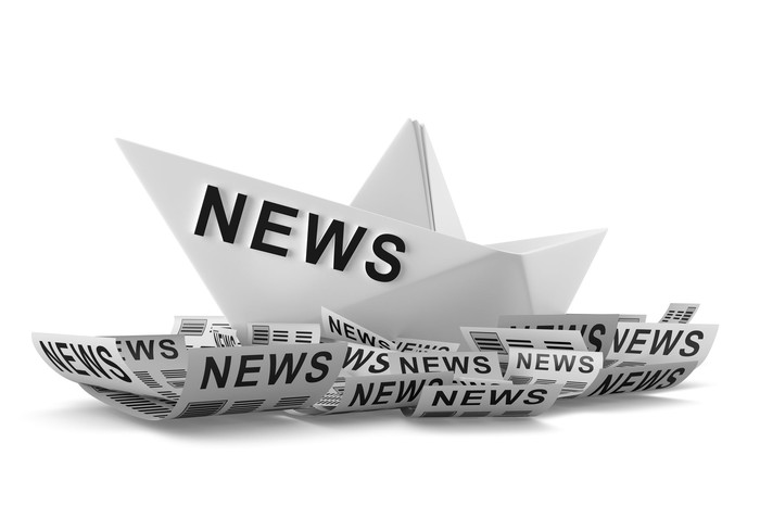 "A paper boat that says ""news"" riding on paper waves."