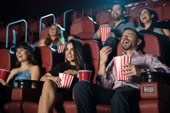 Young men and women sitting in a movie theater and enjoying the show.