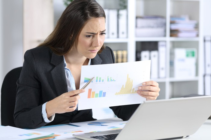 A young businesswoman frowns, holding up a paper full of charts to her laptop's webcam.