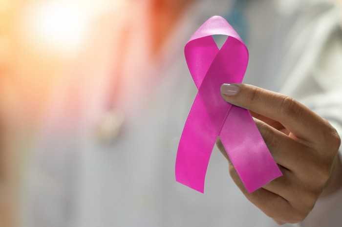 Physician holding a pink ribbon symbolizing breast cancer awareness