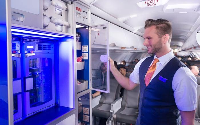 A JetBlue flight attendant checks stations with passengers on a JetBlue plane.