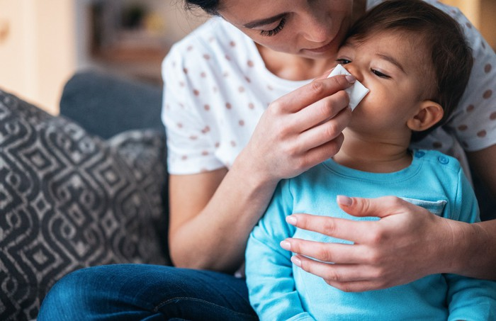 Woman wiping child's nose