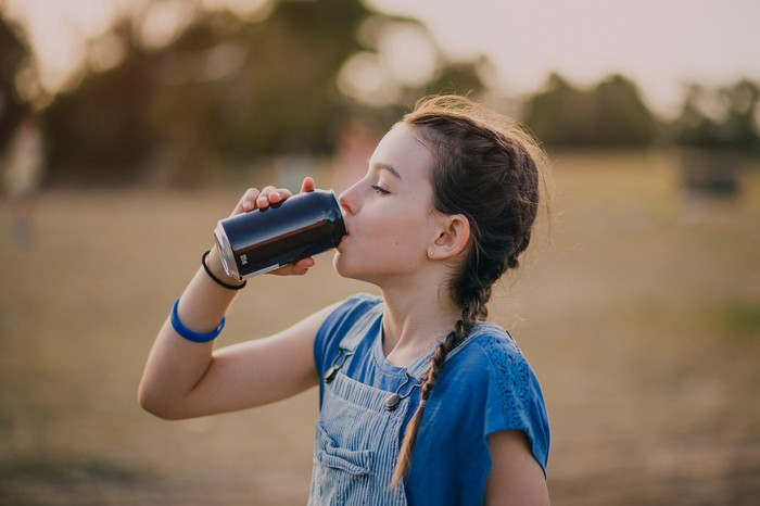 Girl drinking a can of cola.