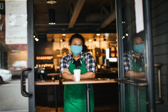 Starbucks barista wearing a mask and serving a customer.