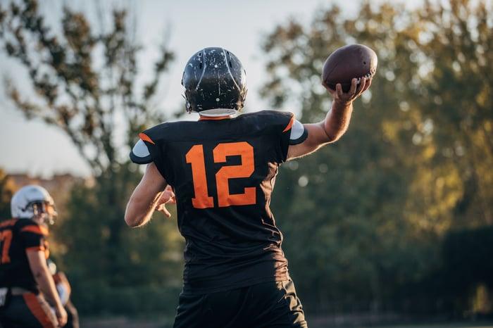 Quarterback throwing a football to a receiver.
