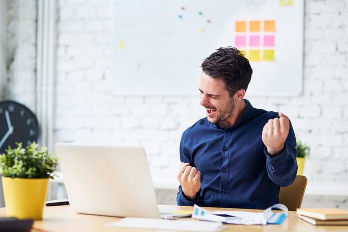 Cheering man looking at a laptop.