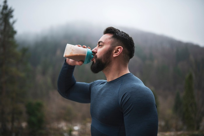 An outdoor fitness enthusiast drinking a protein shake in front of a misty, forested hill.