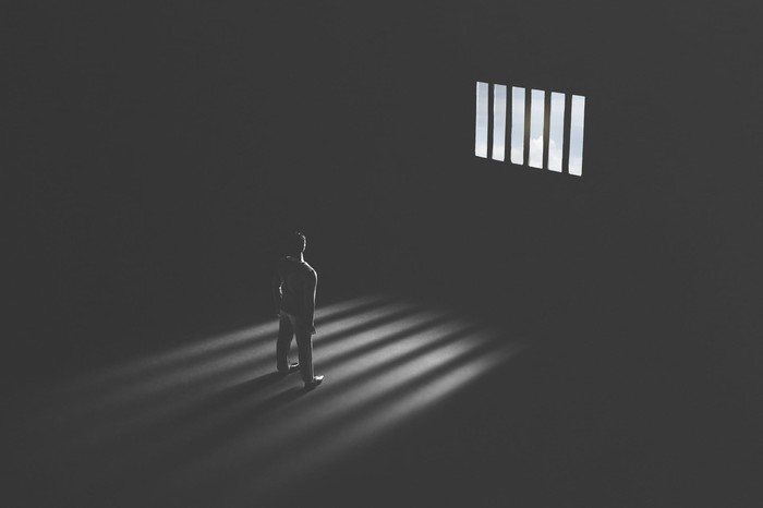 Black and white picture of a prisoner staring through a jail cell window