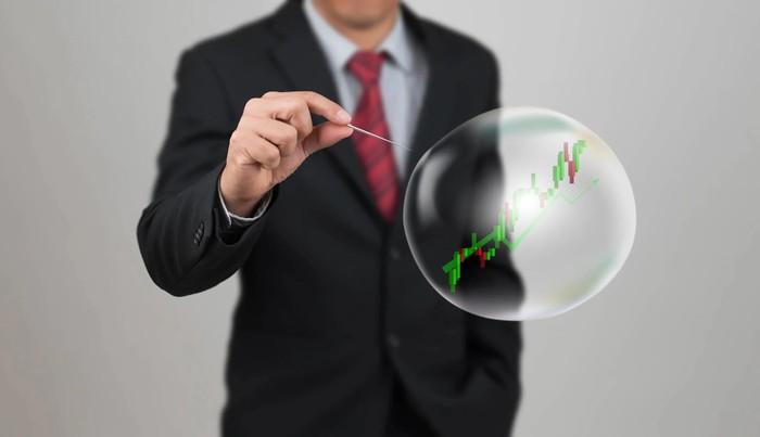 Person wearing suit holding pin in front of bubble with stock chart inside.