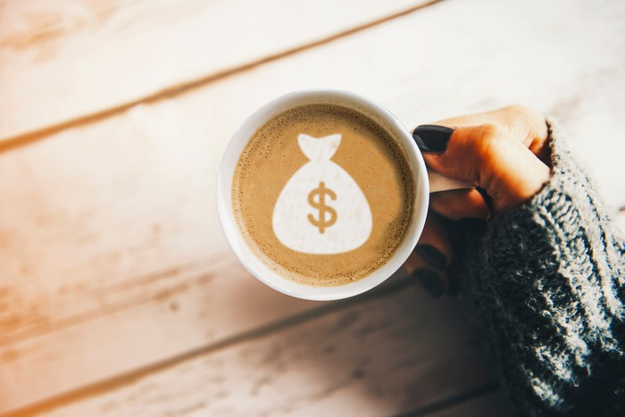 A woman's hand with black nail polish holding a coffee cup with a money bag symbol on the coffee surface.