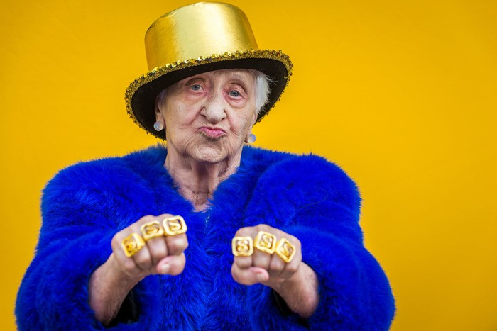 Gray haired woman wearing blue fur suit, gold top hat and gold rings with dollar signs.