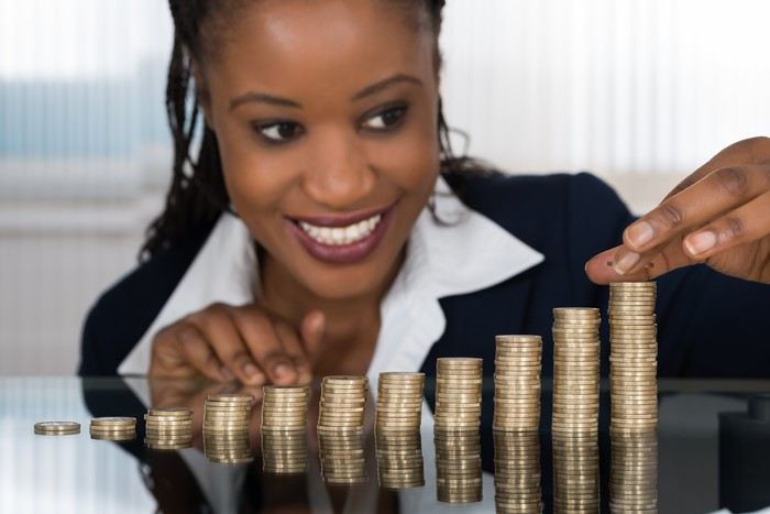 Investor looking at a rising stack of coins.