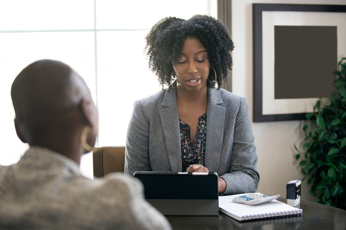 Black female businesswoman in an office with a client giving legal advice about taxes.