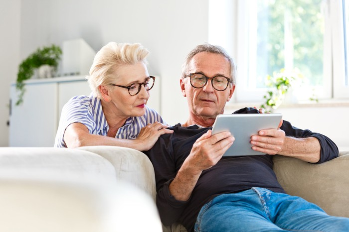 An elderly couple sitting on a couch looking at data on a tablet.