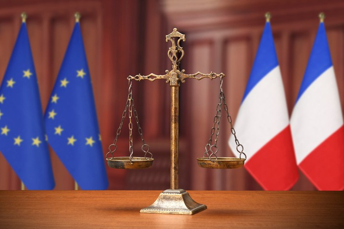 Scales of justice with EU and French flags in the background