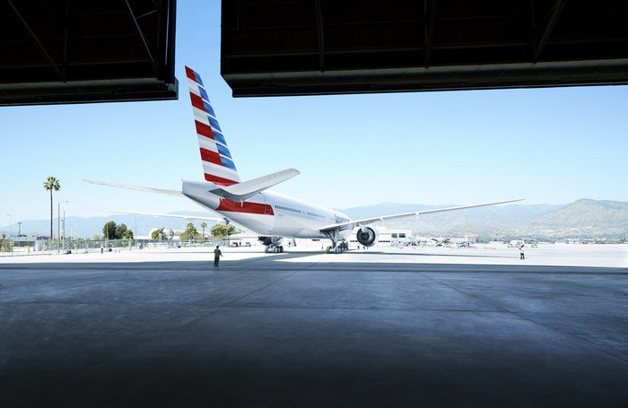 An American Airlines plane emerges from a hanger.