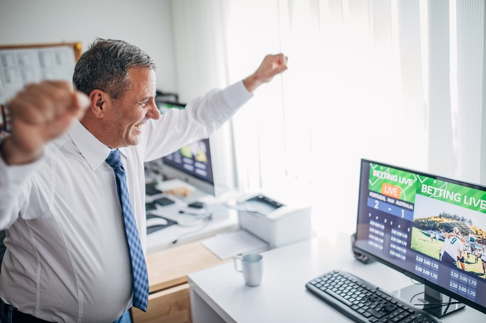 A happy-looking businessman betting on sports in his office, with sports betting open on his computer.