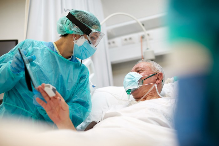 Older man in a hospital bed with a healthcare professional standing next to him