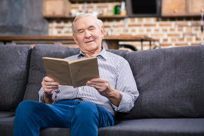 Older person sitting on a couch, reading a book
