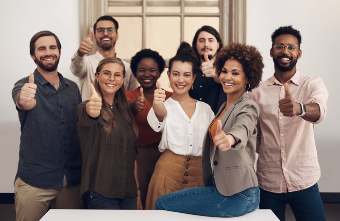 A diverse, happy workforce pose with their thumbs in the air.