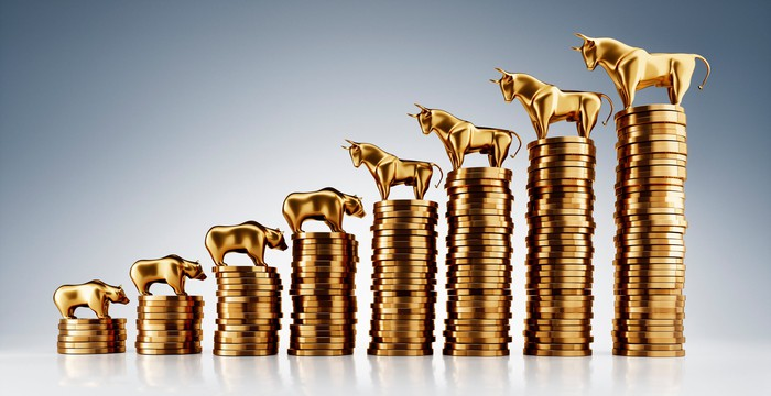 Bull and bear figurines on top of ascending stacks of coins.