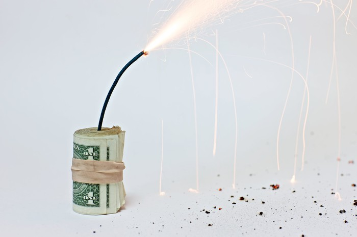 A roll of dollar bills, wrapped in a rubber band, with a lit fuse sticking out of it.