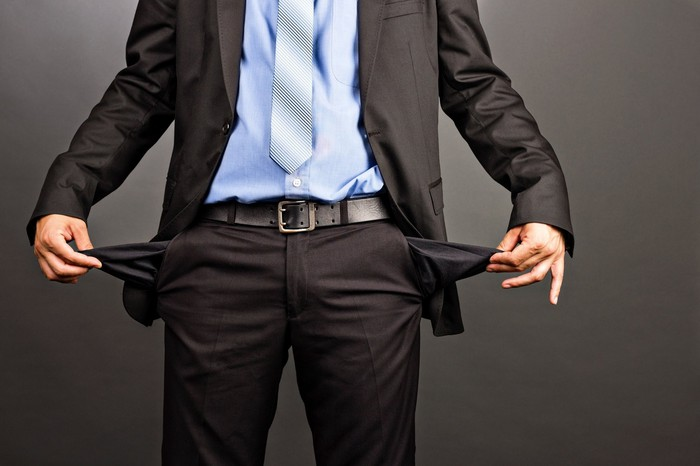 A man in a suit holding out his empty pants pockets