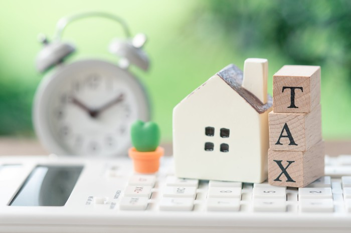 A model house is placed on the wooden word TAX.