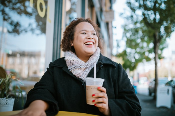 Smiling woman holding coffee beverage outside a coffee shop